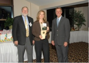 Leslie Schreiber accepting her award from VBM Publisher John Boutin and Vermont Lieutenant Governor Phil Scott.